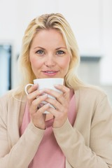 Beautiful young woman with coffee cup in kitchen