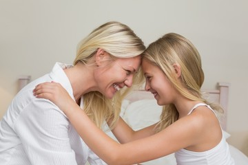 Mother and daughter with head to head in bedroom