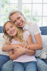 Happy mother embracing daughter on sofa