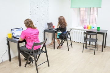 Two women sitting at working place in office room
