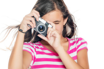 Young girl using a compact camera isolated on white