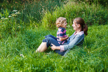 Little boy and his mother sitting on grass in summer forest