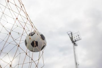 Fototapeta Soccer football in goal net