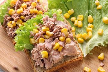 Sandwich with tuna and corn on wood