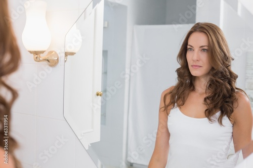 woman looking at herself in the bathroom mirror fotolia com の
