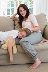 Mother looking at daughter sleeping on her lap