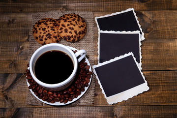 Coffee cup, cookies and old blank photos, on wooden background