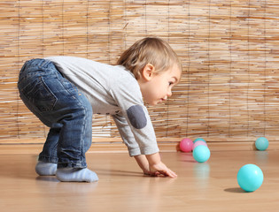 Little boy playing with balls.