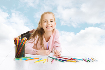 Girl drawing, looking for painting idea. Smiling child blue sky