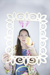 Woman wearing rabbit ears posing with Easter egg