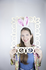 Woman wearing rabbit ears posing with picture frame