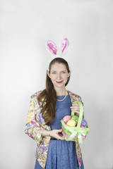 Young woman wearing rabbit ears holding Easter basket
