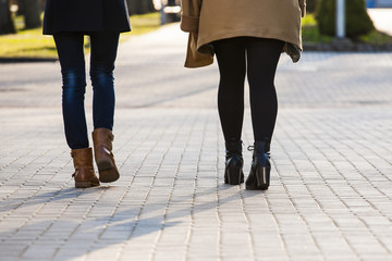 Young women walking on the sidewalk.