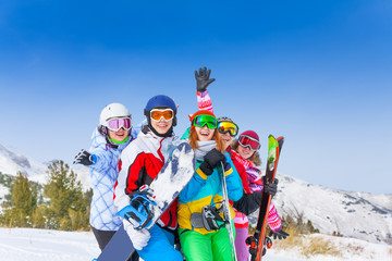 Five happy friends with snowboards and skis