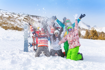 Six friends with snowboards and skis throwing snow