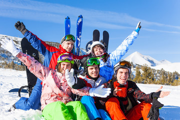 Positive friends with snowboards lifting hands up