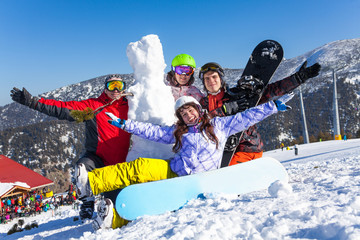 Four happy friends with snowboard and snowman