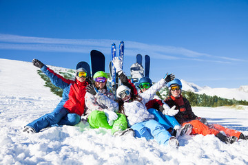 Happy friends sitting with snowboards and skis