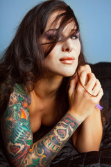 Beautiful girl with stylish make-up and tattooed arms,..