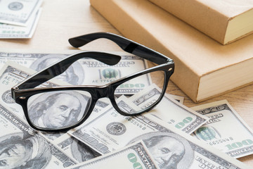 Glasses on dollar bills and books