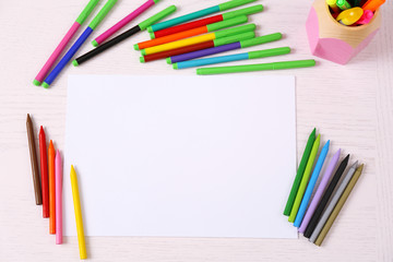 Colored pencils and blank paper sheet on wooden table