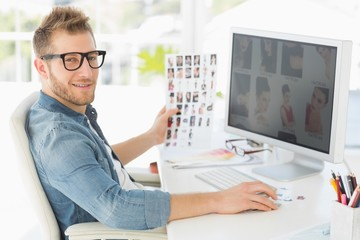 Handsome editor working at his computer smiling at camera