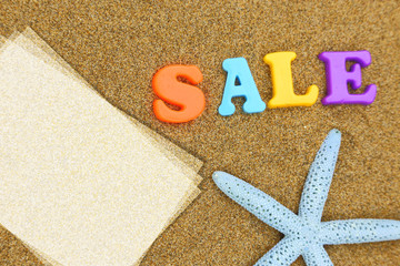 Sale text and starfish with copy-space on sand