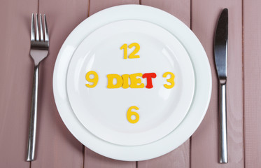 Plate with inscription diet on wooden table close-up