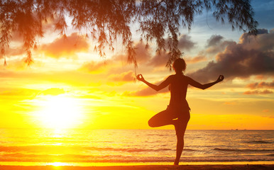 Young woman silhouette practicing yoga on beach at sunset.
