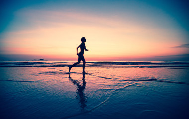 Blured silhouette of a woman jogger on the beach at sunset.
