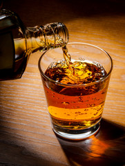 Fototapete - brandy or whiskey pouring into glass