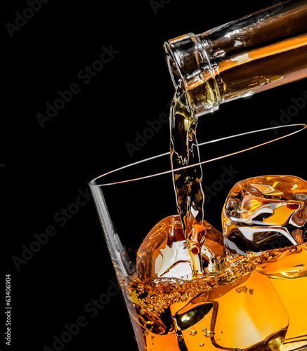 Wall mural Pouring whiskey drink into glass
