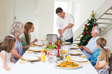 Father serving Christmas meal to family