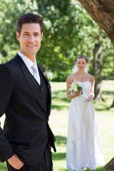 Happy groom with bride standing in background at garden