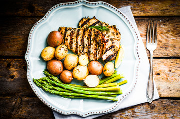 Wall Mural - Grilled chicken with potatoes and asparagus on wooden background