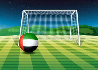 A soccer ball at the field with the UAE flag