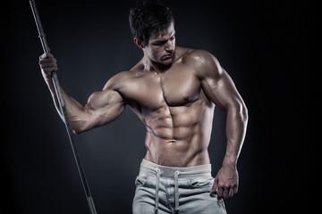 Muscular bodybuilder guy doing posing with dumbbells over black