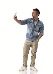 Full body shot of young man taking photo with cellphone
