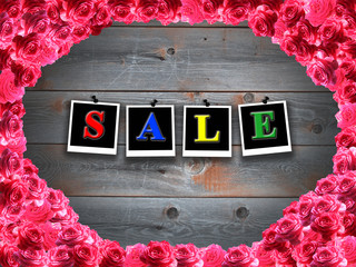 inscription sale and frame from roses on background of boards