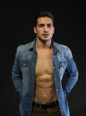 Latin young man with open denim shirt on naked chest.
