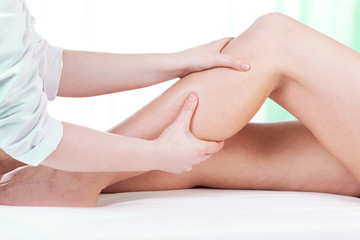 Hands massaging female leg
