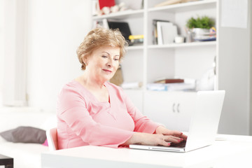 Close-up of a senior woman with laptop