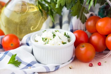 White soft cheese, feta, goat in bowl with tomatoes, parsley