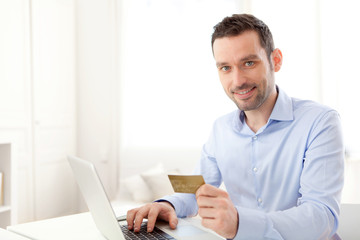 Young business man paying online with credit card