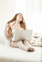 curly woman lying in bed with laptop