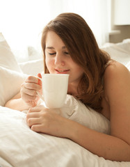 portrait of pretty woman drinking coffee in bed