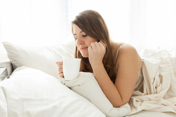 cute woman lying in bed with cup of coffee