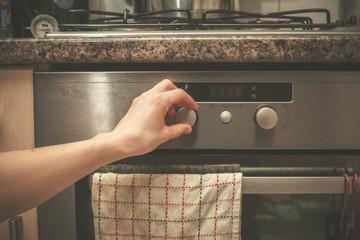 Hand turning knob on stove