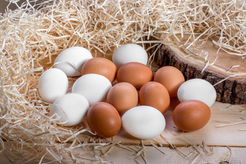 Brown and white eggs in the straw nest on wooden background