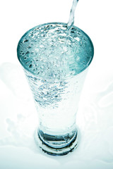 Pour water into a glass on a white background.